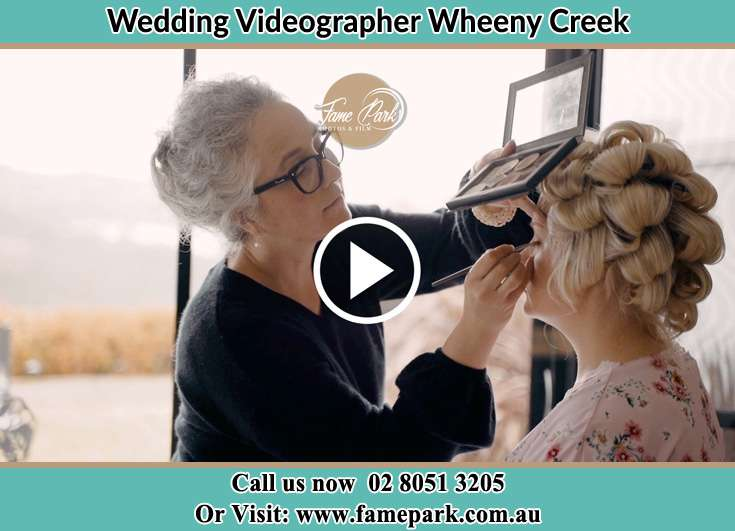 The makeup artist doing the finishing touch on the Bride's face Wheeny Creek NSW 2758